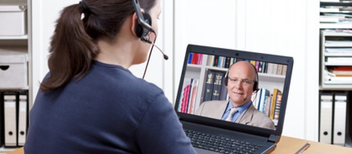 Woman with pen and paper and a headset in front of her laptop making a video call with her friendly professor, text space